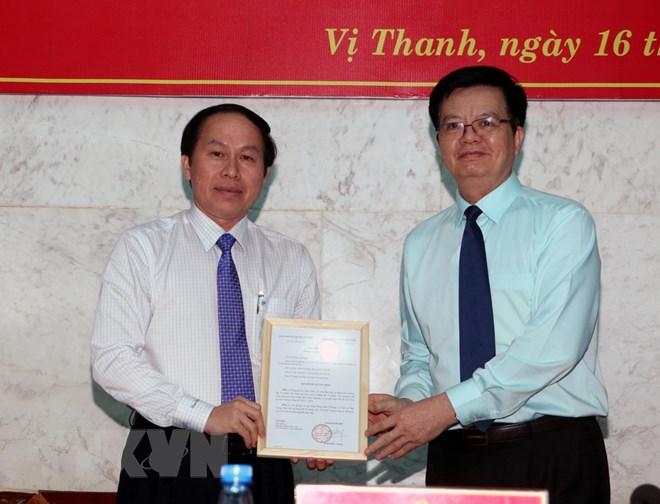 Ông Mai Văn Chính, Phó Trưởng ban Tổ chức Trung ương trao quyết định cho ông Lê Tiến Châu. (Ảnh: Duy Khương/TTXVN)