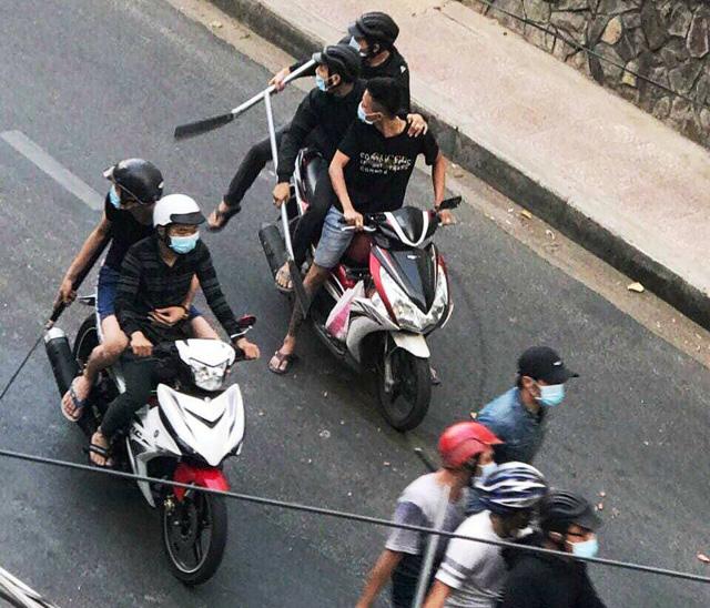 Nhóm thanh niên đeo khẩu trang, cầm hung khí trên đường phố - Ảnh: FACEBOOK THINH PHUC