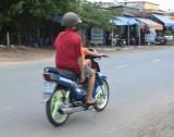 Người đàn ông ngồi sau để bé gái điều khiển xe máy chạy băng băng trên đường