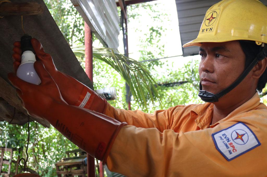 Nhân viên điện lực hướng dẫn và thay thiết bị điện tiết kiệm điện cho người dân