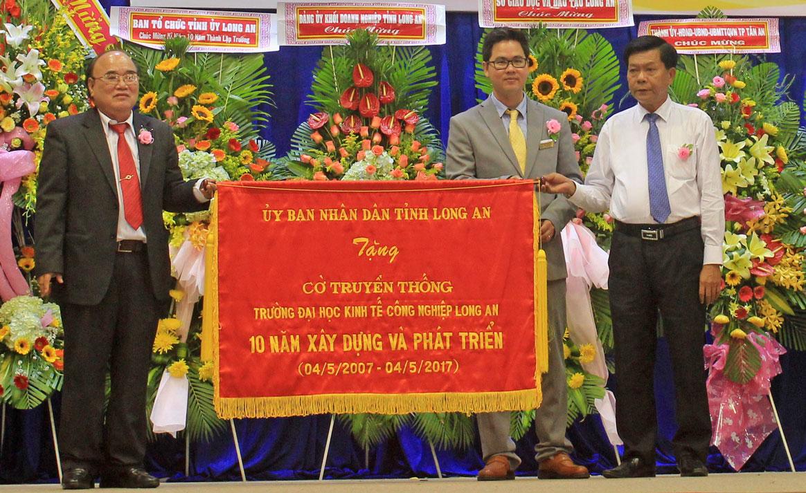 Chủ tịch UBND tỉnh - Trần Văn Cần (bìa phải) trao cờ truyền thống cho Trường DLA