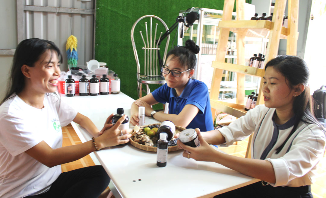 Chị Huỳnh Thị Kim Hoàng (bìa phải) đang tư vấn cho khách hàng về công dụng của dầu gội không bọt Yopoo