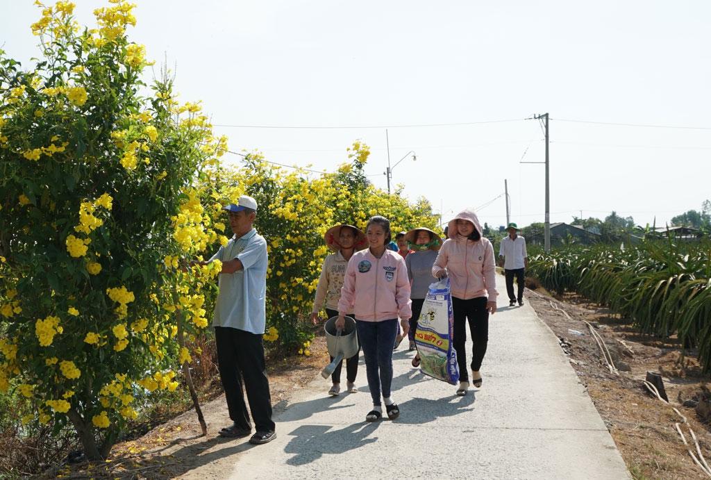 Người dân ấp Thanh Quới xã Thanh Phú Long dọn dẹp vệ sinh môi trường trên tuyến đường hoa