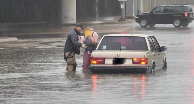 Nhân viên cứu hộ hỗ trợ một công dân bị mắc kẹt trong nước lũ. (Nguồn: accuweather.com)