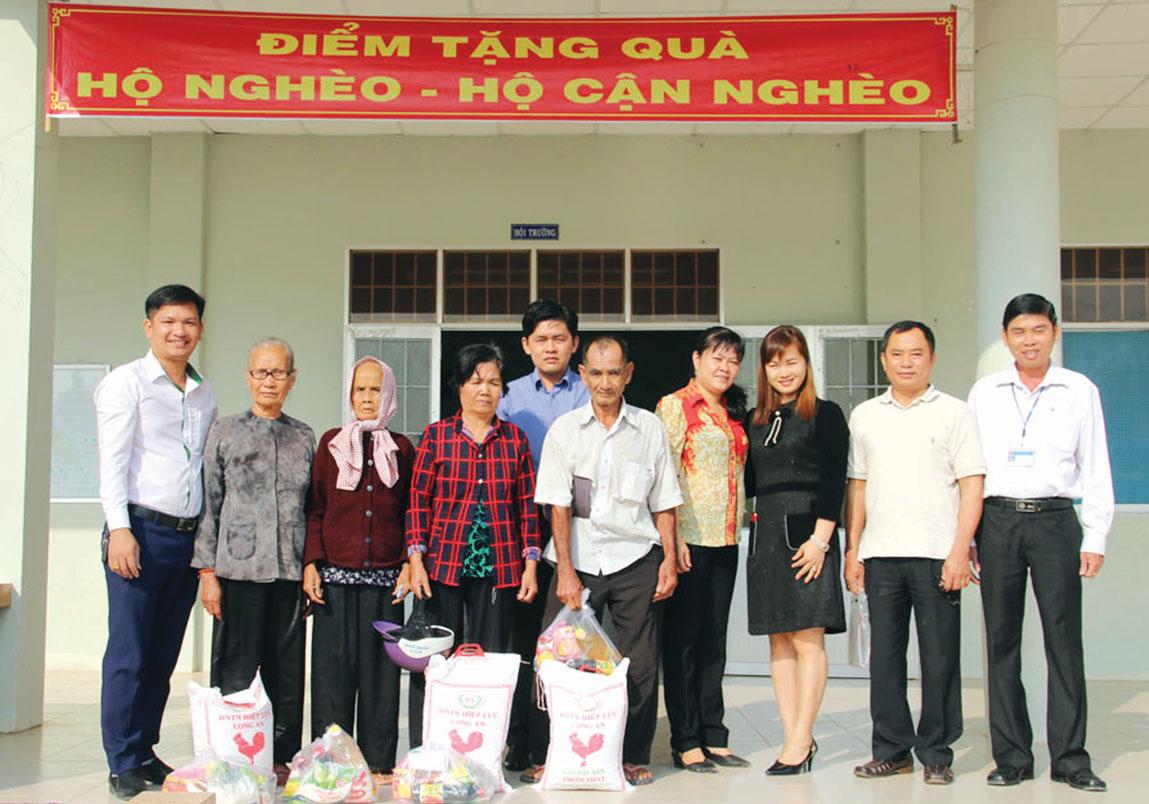 Nguyên Tổng Biên tập  Báo Long An - Lê Công Đấu (thứ 2,  phải qua) tặng quà cho người nghèo
