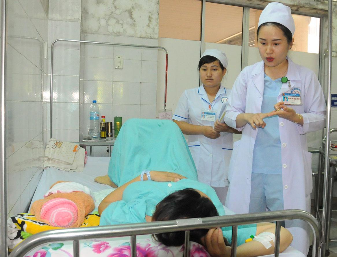 Nhân viên y tế hướng dẫn sản phụ biện pháp cho trẻ bú đúng cách