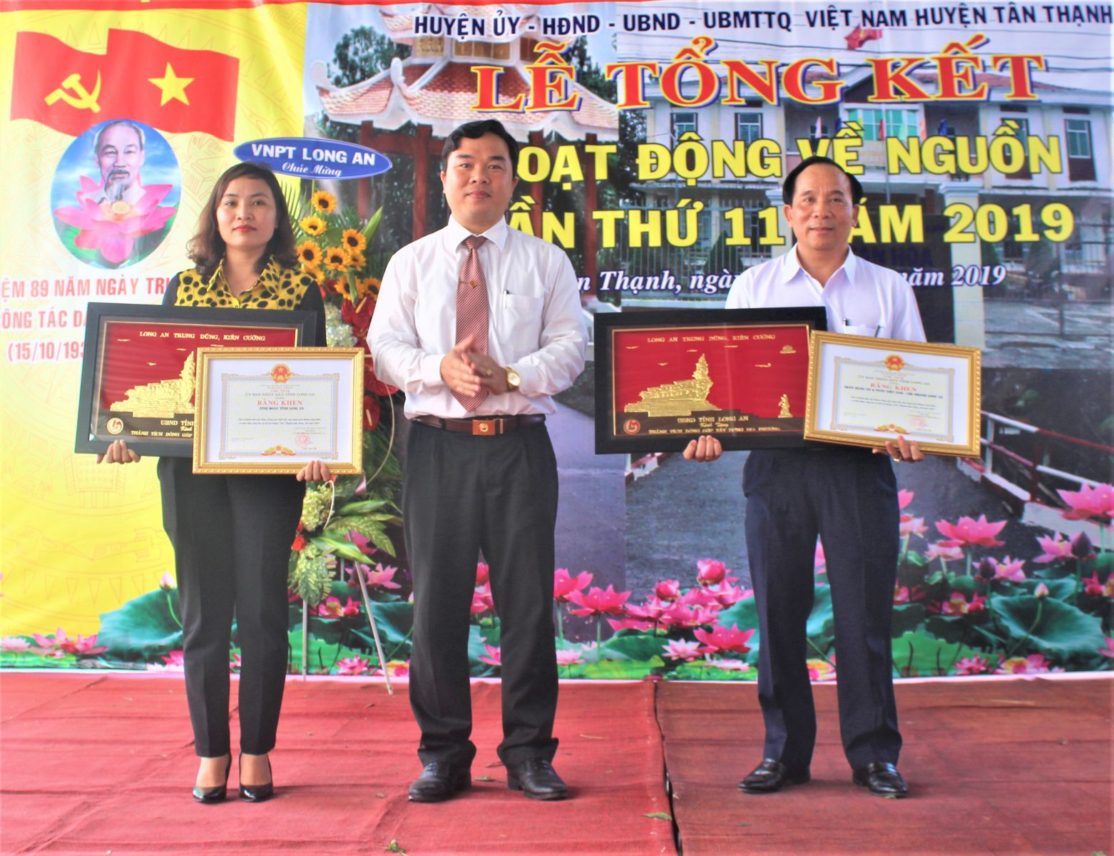 Secretary of Tan Thanh district Party Committee - Bui Quoc Bao (C) awards the Certificate of Merit of Long An provincial People's Committee to individuals and collectives with good achievements in the ancestor-returning activities 2019