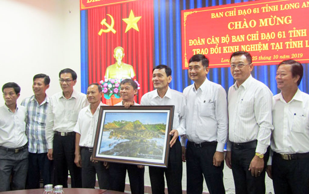 """The Mission of Steering Committee 61of Phu Yen Province presents to Long An Province a photo of """"Ghenh da dia"""" - one of the famous tourist destinations of Phu Yen province"""