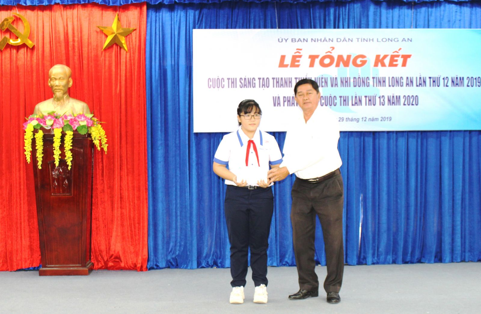 Vice Chairman of the provincial Vietnam Association for Promotion of Studies - Vo Le Tuan presents gifts to Le Thanh Truc – a student of Hau Nghia Secondary School