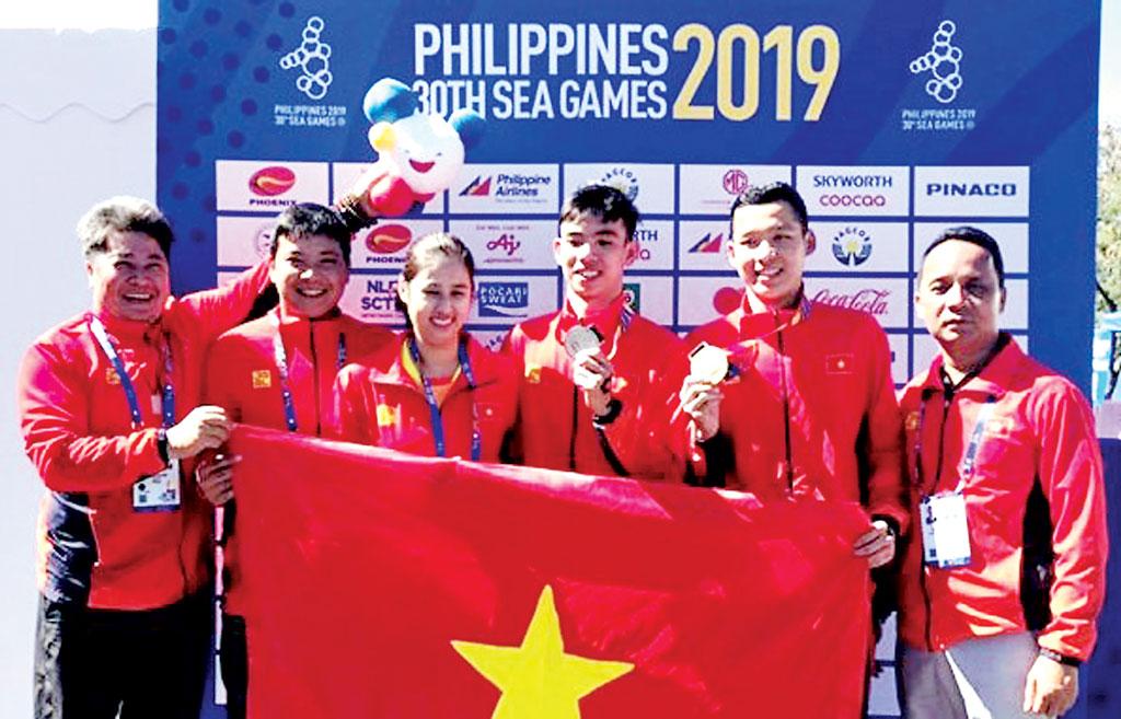 Vận động viên Trần Tấn Triệu (thứ 2, phải qua) cùng Ban Huấn luyện môn Bơi lội ăn mừng sau khi nhận Huy chương Vàng SEA Games