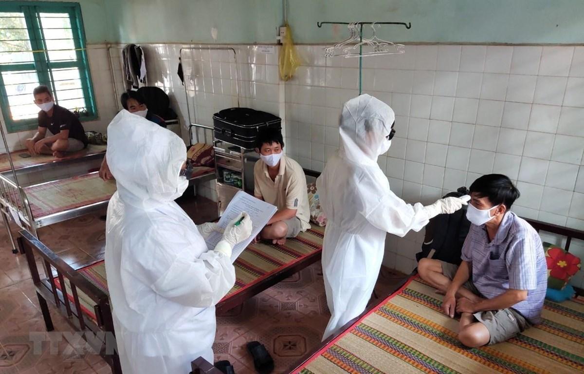 Nhân viên y tế đo thân nhiệt, kiểm tra sức khỏe đối với công nhân phải cách ly. (Ảnh: Dương Chí Tưởng/TTXVN)
