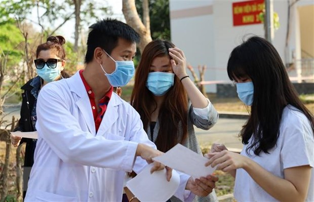 Bác sỹ Bệnh viện dã chiến Củ Chi hướng dẫn và căn dặn bệnh nhân tự cách ly tại nhà sau xuất viện. (Ảnh: Đinh Hằng/TTXVN)