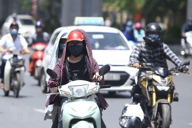 Người dân trang bị các vật dụng chống nắng cần thiết khi ra đường. (Ảnh: Minh Quyết/TTXVN)
