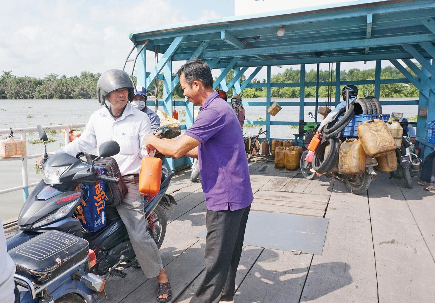 Thuyền trưởng Châu Bảo Đức nhắc nhở hành khách sử dụng dụng cụ cứu sinh cầm tay khi qua phà Vàm Thủ