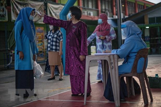 Kiểm tra thân nhiệt phòng lây nhiễm COVID-19 tại một trường học ở Kuala Lumpur, Malaysia. (Ảnh: AFP/TTXVN)