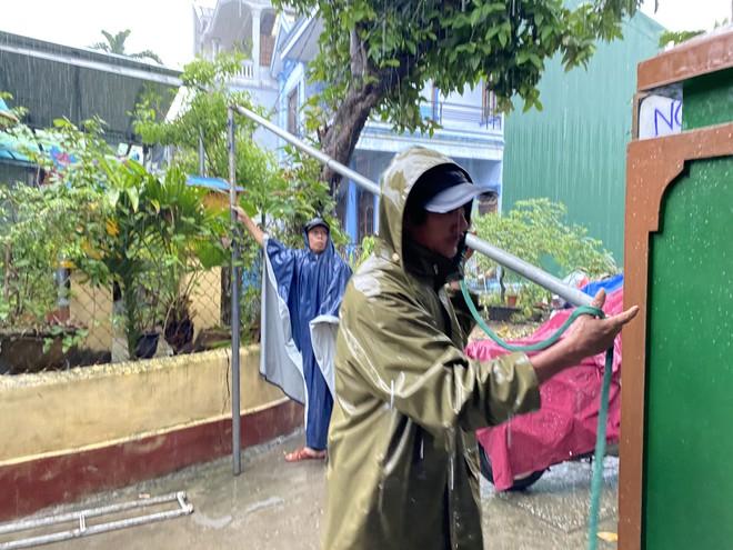 Dưới cơn mưa lớn, nhiều người khẩn trương dựng mái che chờ đưa thiếu tá Phúc về với gia đình. Ảnh: Huy Đạt
