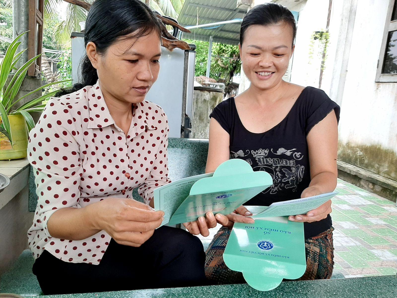 Chị Trần Thị Mộng Tuyền (phải) xem sổ bảo hiểm xã hội tự nguyện của hai vợ chồng là tài sản, một loại tài sản bền chắc và không thể mất mát đi đâu được