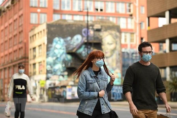 Người dân đeo khẩu trang phòng lây nhiễm COVID-19 tại Manchester, Anh. (Ảnh: AFP/TTXVN)