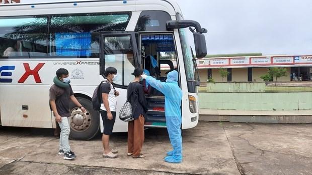 Tiếp nhận và kiểm tra thân nhiệt cộng đồng người Việt nhập cảnh để đưa về cách ly tập trung. (Ảnh: TTXVN phát)