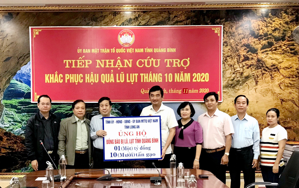 Vice Chairman of the Long An People's Committee - Pham Van Canh (5th, R) hands over a symbolic board of money and gifts to Quang Binh