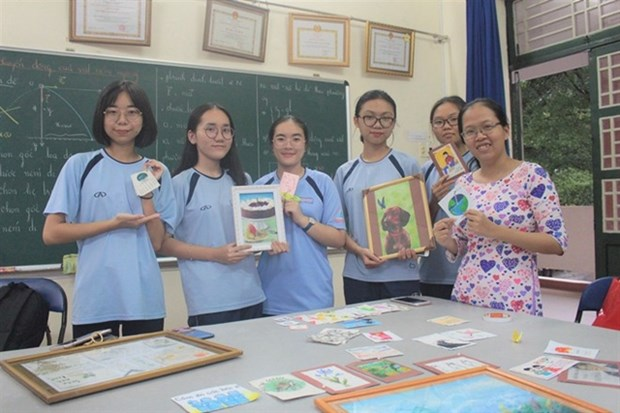 Nguyen Tran Quynh Phuong (right, first), a chemistry teacher at Nguyen Huu Huan High School, Thu Duc District, and her students show off some of the paper and hand-made souvenirs made from bagasse. (Photo thanhnien.vn)