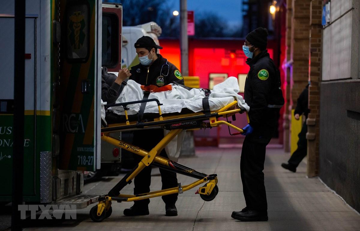 Nhân viên y tế chuyển bệnh nhân nhiễm COVID-19 tới bệnh viện ở New York, Mỹ. (Ảnh: THX/TTXVN)