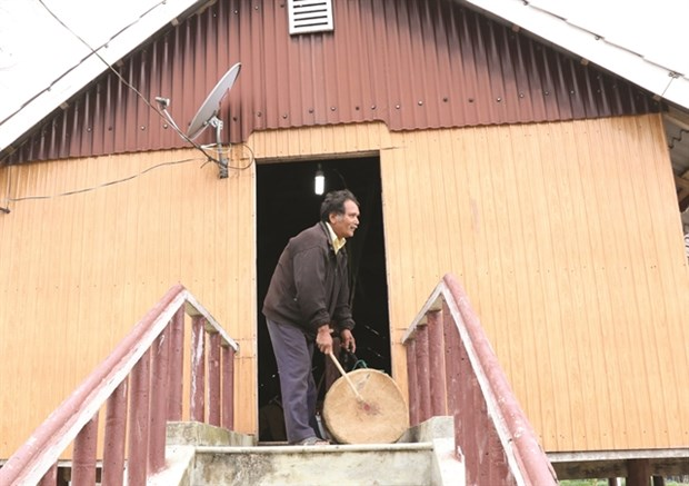 The oldest man in the village beats a drum to urge people to gather around the communal house to organise the worship ceremony. (Photo: VNA)