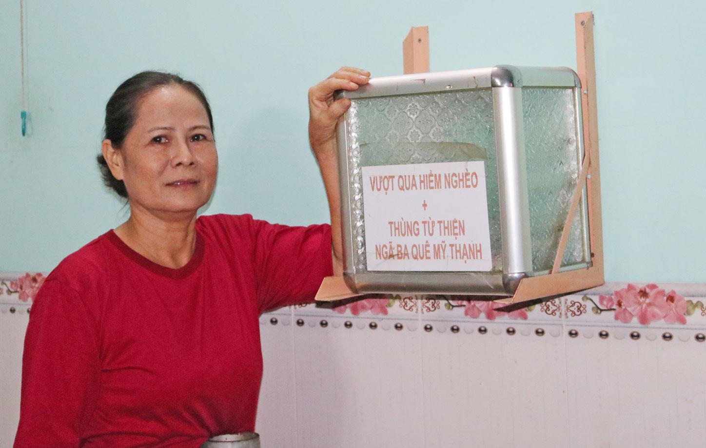 Bà Đoàn Thị Út bên thùng từ thiện đã tồn tại 10 năm qua, góp phần giúp những gia đình có hoàn cảnh khó khăn